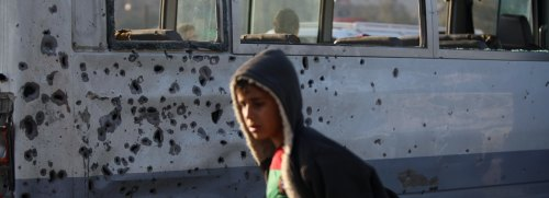A boy walks past by a bus damaged from s